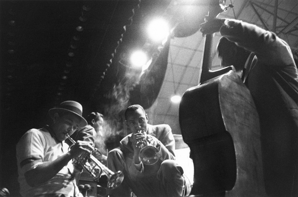 Black and white photograph of three men playing instruments in a smoky room