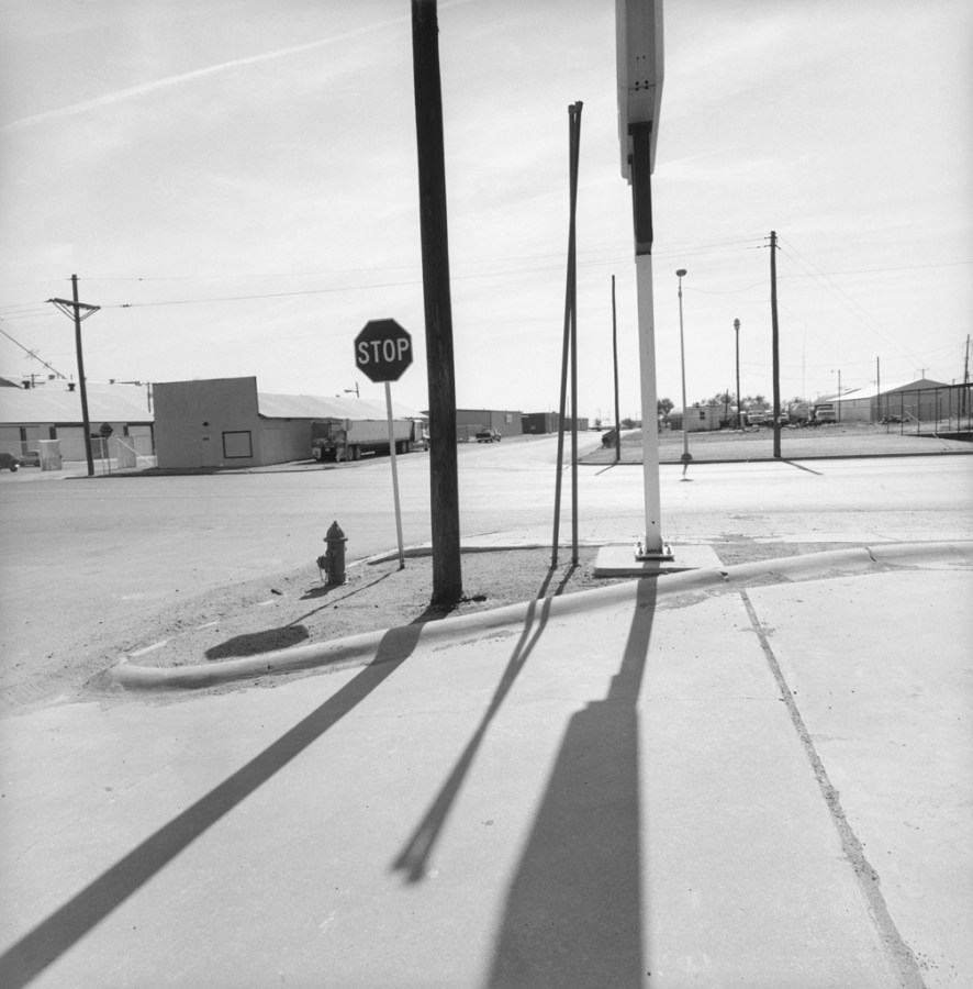 A black and white photograph of roadside signs and their shadows