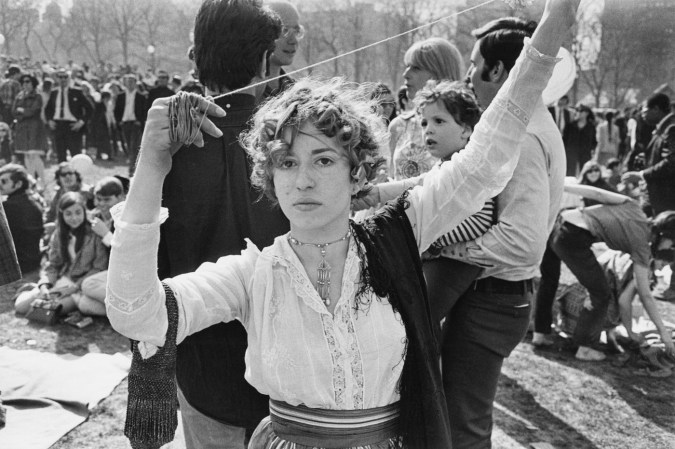 Black-and-white portrait of a woman with short curly hair holding a piece of yarn aloft with two hands