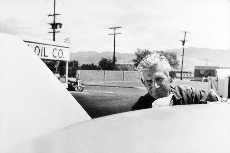 Black-and-white photograph of a man with white hair peering over the roof of a car in a parking lot
