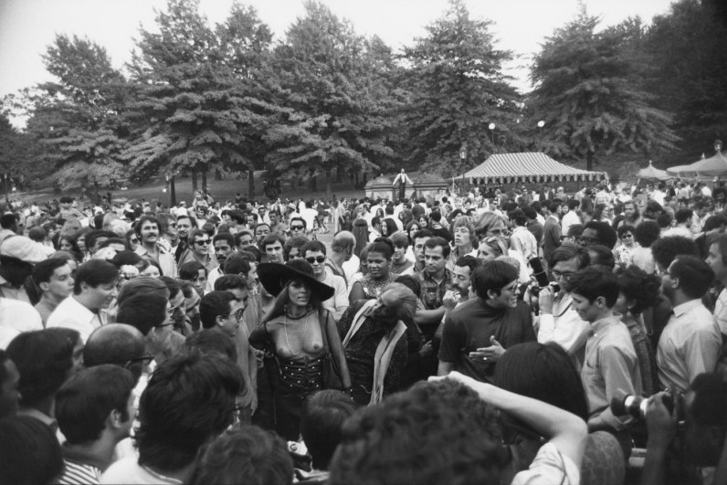 Black-and-white-photograph of a bare-breasted woman wearing a large hat in a crowd of people in a park