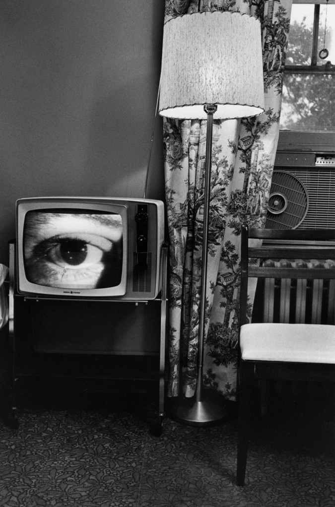 Black-and-white photograph of room with a lamp a chair and a television with a close up of an eye on screen