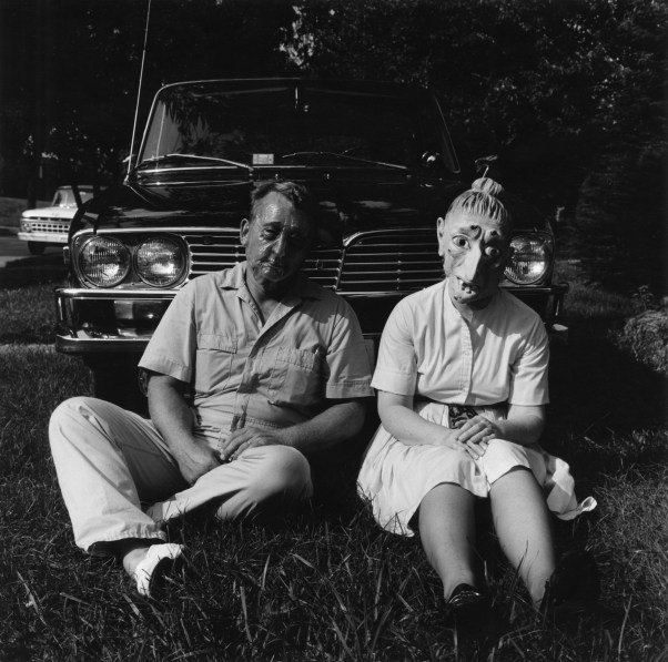 Black-and-white photograph of a couple wearing rubber masks seated in the grass in front of a car
