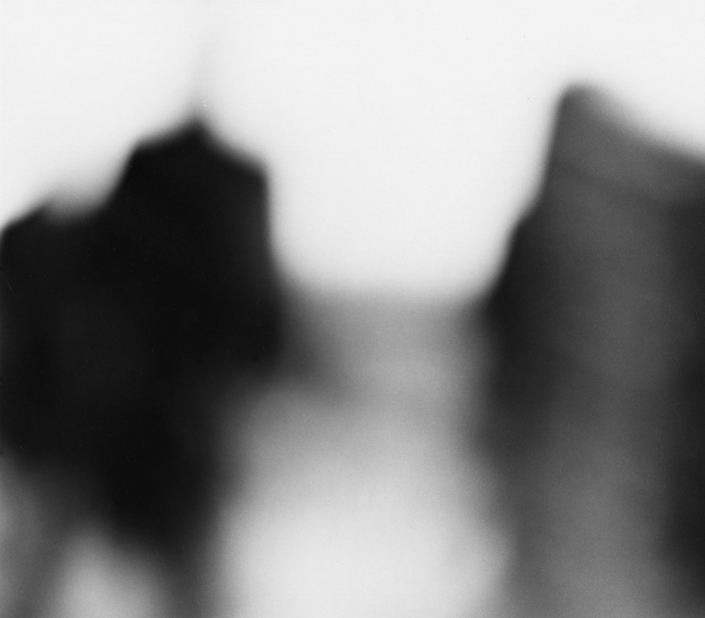 Black-and-white out-of-focus photograph of two dark figures walking