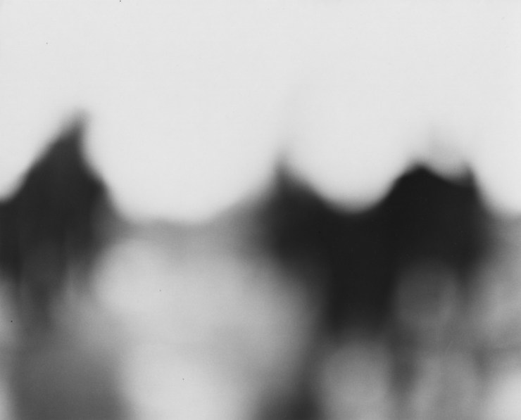Black-and-white out-of-focus photograph of three dark figures standing apart from one another