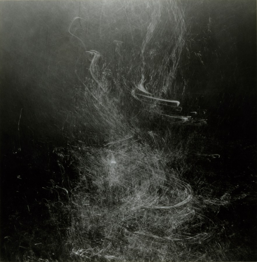 Square black-and-white long-exposure photograph of bubble trails rising underwater