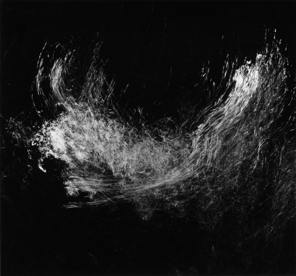 Square black-and-white long-exposure photograph of light reflecting off of splashing water