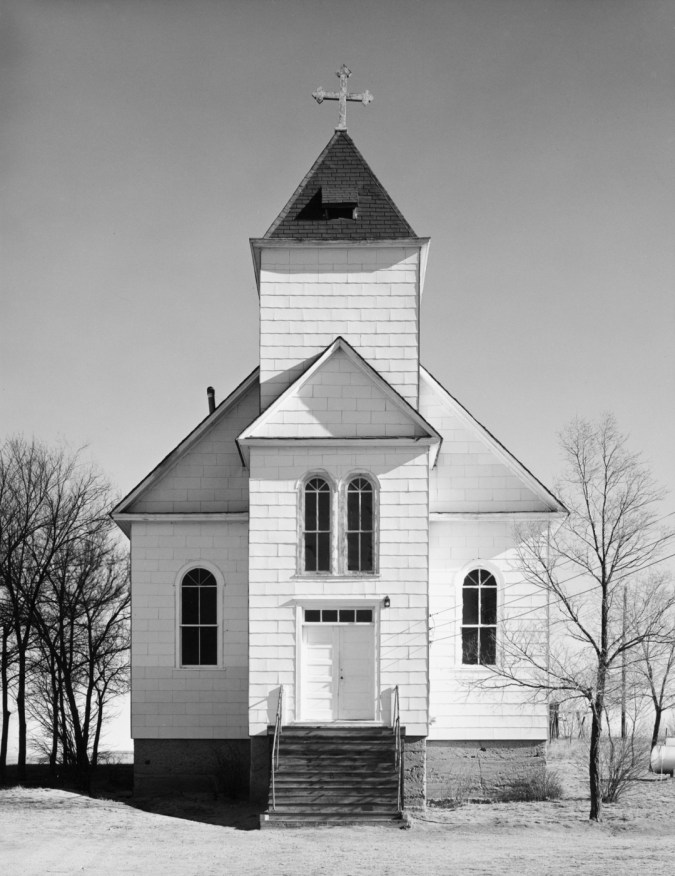 A vertical black and white photograph of an old wooden church with trees at each side and a clear bright sky.