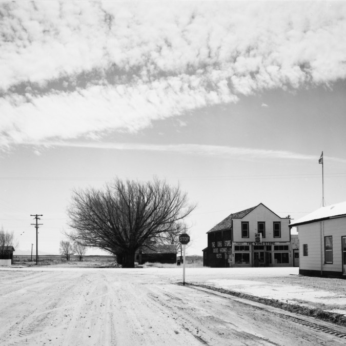 A black and white photograph of a small town with dirt roads, simple wooden buildings, a large tree in the left portion of image, and bright cloudy sky.