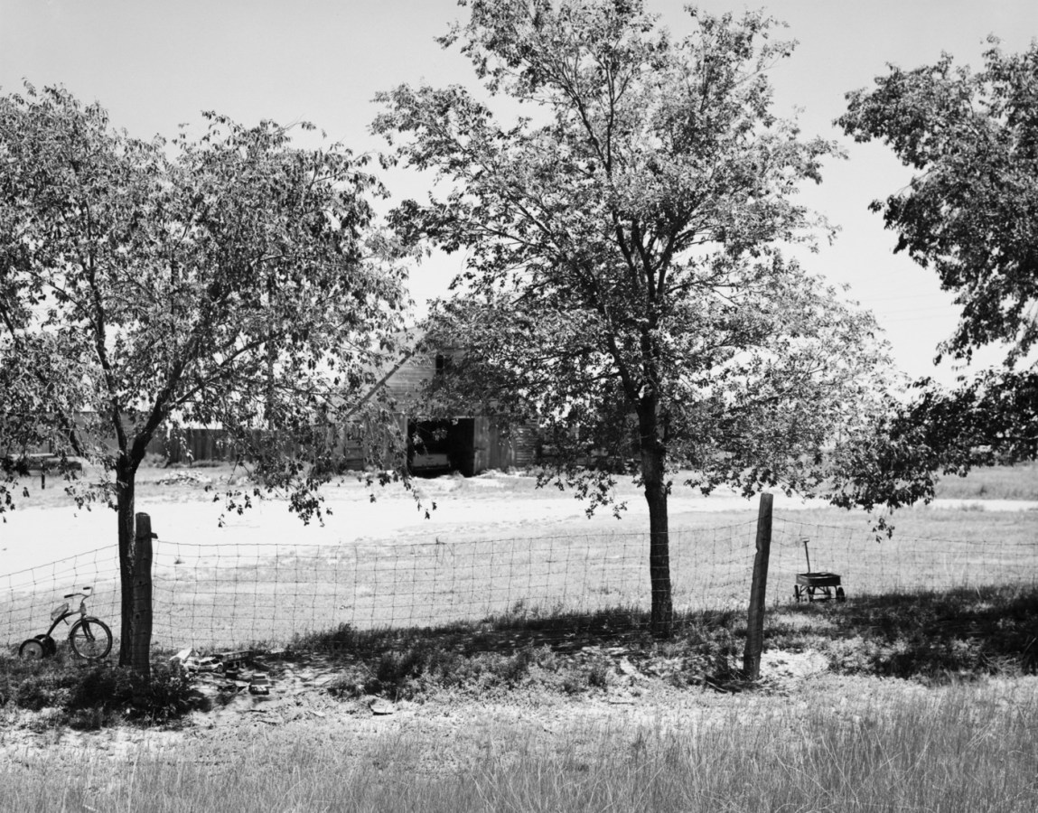 A black and white photograph with trees, a wire fence, a tricycle at the left side of the image, a wagon at the right side of the image and a barn in the background.