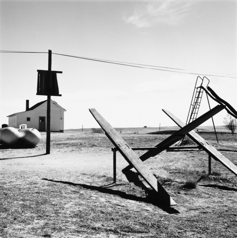 A black and white photograph of a playground with teeter totters, a slide, and a telephone pole with wires. A wooden structure in the background against a bright clear sky.