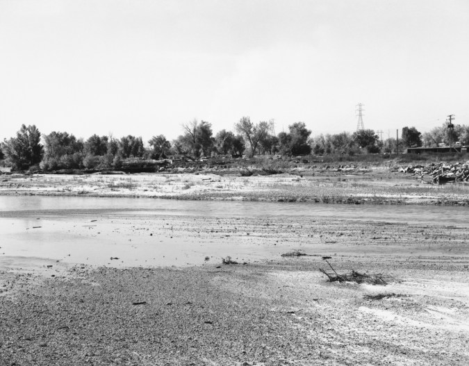 A black and white photograph of a river with trees and telephone wires in the background.