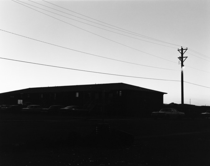 A black and white photograph of an apartment building and parked cars in shadow against a clear sky.
