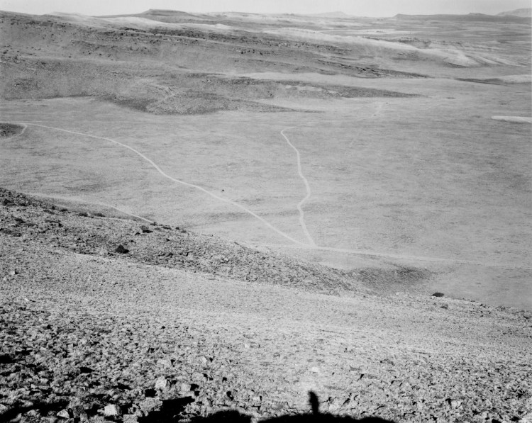 A black and white photograph of an expansive valley with roads running through it with mountains on the horizon.