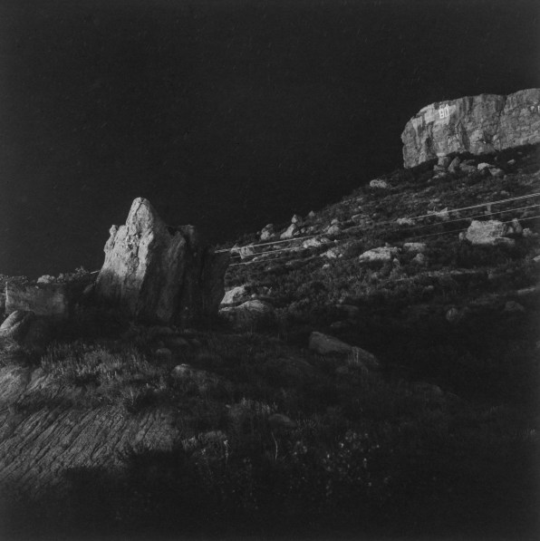 Black-and-white photograph of rock formations and telephone lines at night