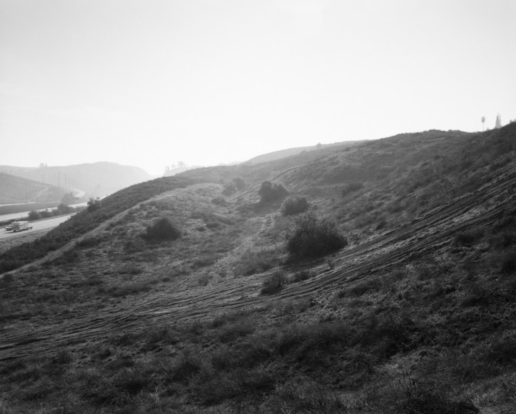 Black-and-white photograph of light streaming over a hillside with a freeway to the left