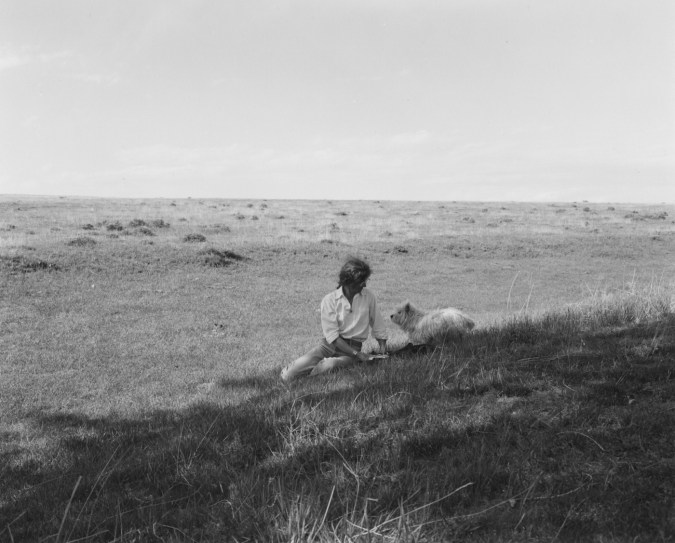 A black and white photograph of a woman and a small white dog sitting in a field.