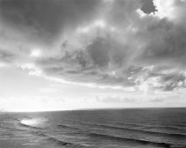 Black-and-white photograph of the ocean with small waves and a cloudy sky with sunlight shining through the clouds