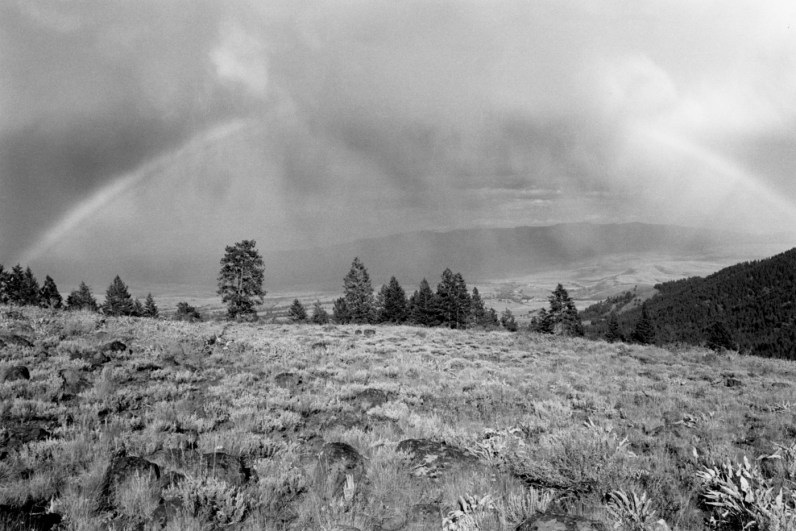 Black-and-white photograph of an open field with trees on the horizon and clouds and a rainbow in the sky
