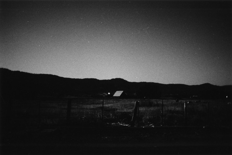 Black-and-white photograph of a vallery at dusk with a fence and a structure in the center fo the frame and mountains on the horizon