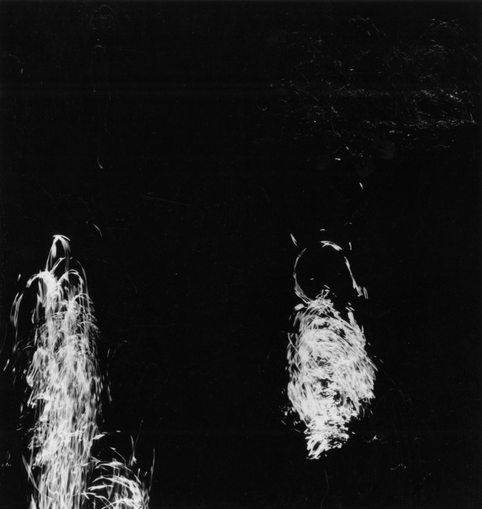 Square black-and-white long-exposure photograph of two trails of light reflecting off of moving water
