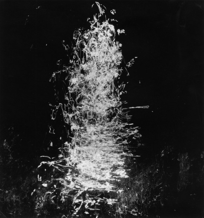 Square black-and-white long-exposure photograph of light trails reflecting off of moving water