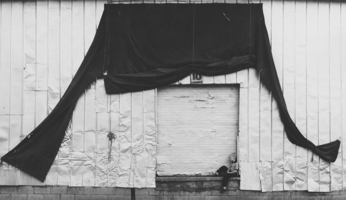 Black-and-white photograph of a young boy sitting in front of a shuttered loading dock