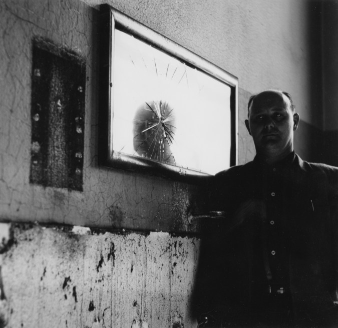 Black-and-white photograph of a man standing next to a cracked mirror