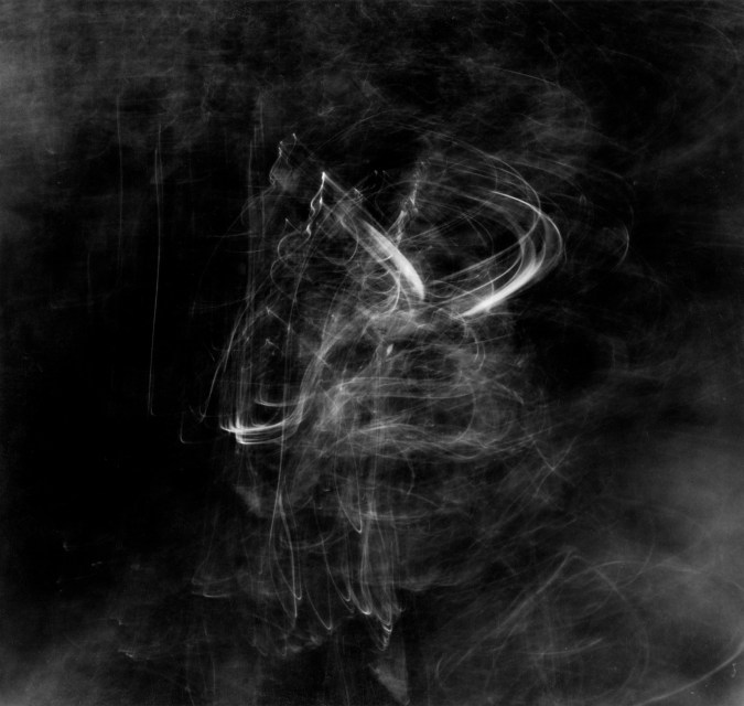 Square black-and-white long-exposure photograph of faint squiggly light trails on moving water