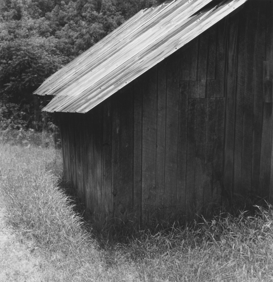 Black-and-white multiple-exposure photograph of the corner of a wooden shed with sloping roof
