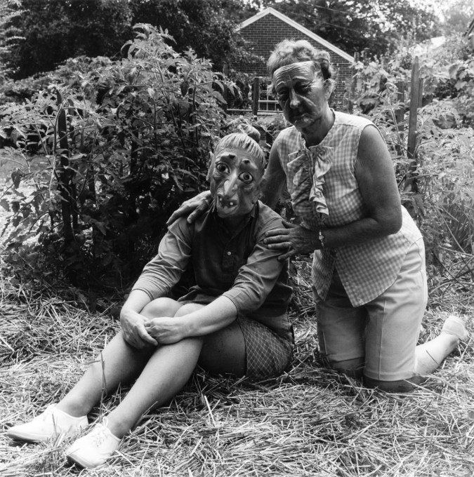 Black-and-white photograph of two people in rubber masks seated before a small garden