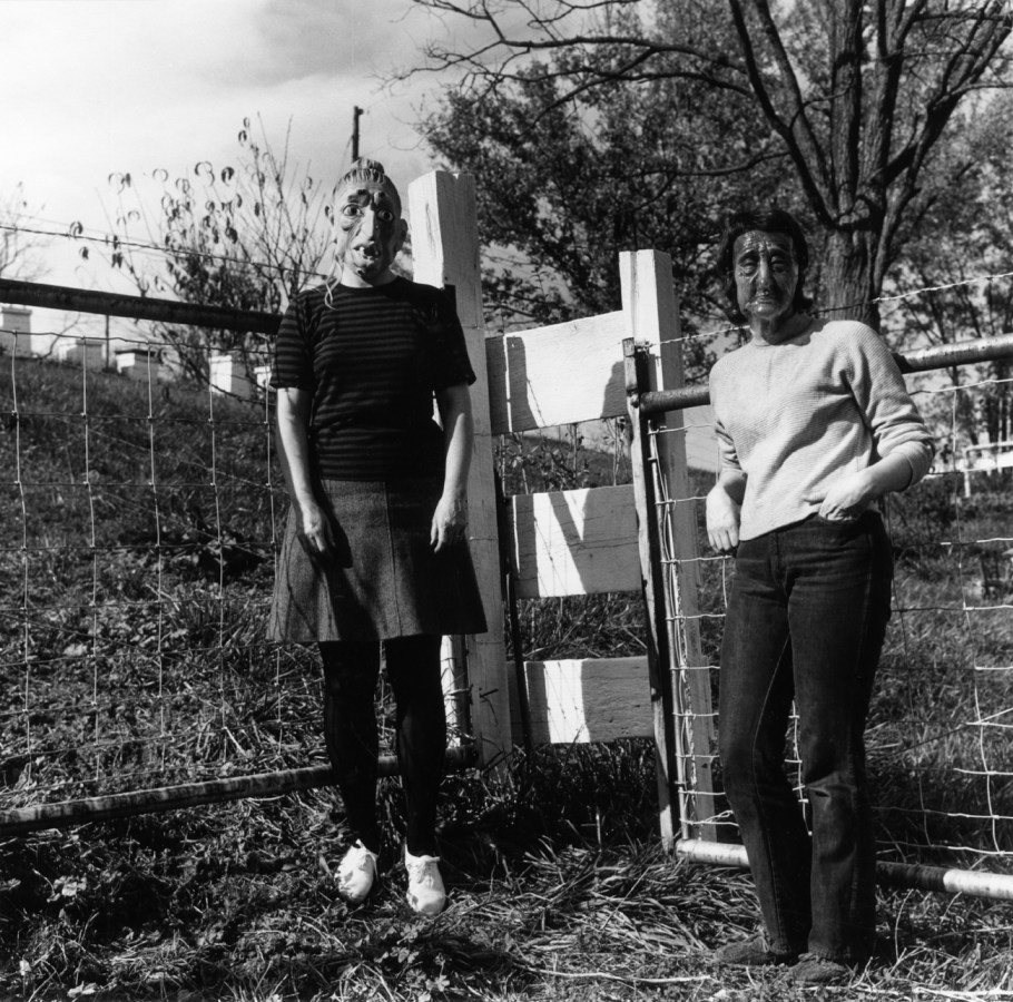 Black-and-white photograph of two people in rubber masks standing by an ajar wooden gate