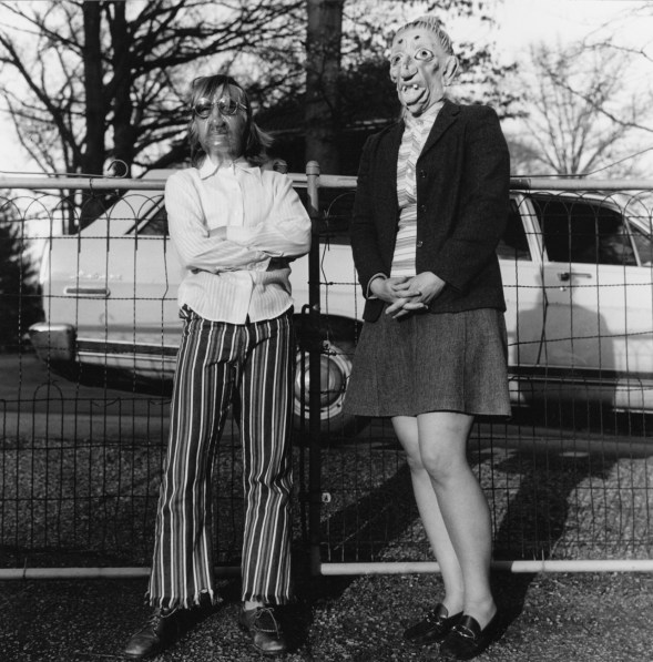 Black-and-white photograph of two people in rubber masks standing in front of a wire fence