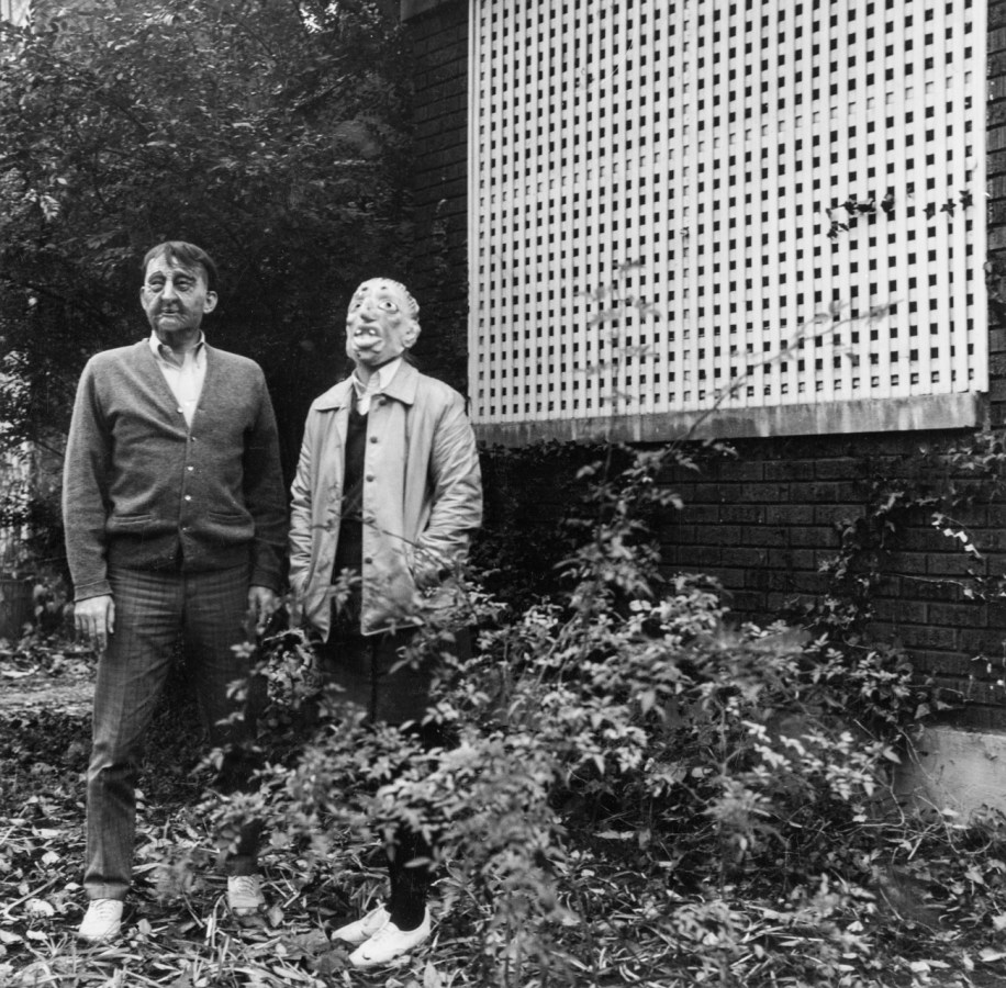 Black-and-white photograph of two people in rubber masks standing next to a lattice-in porch of a brick building