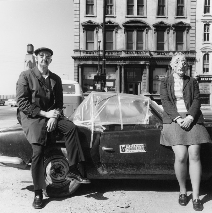 Black-and-white photograph of two people in rubber masks seated on a low convertible car
