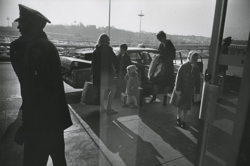 Black-and-white photograph of a family with four children exiting a car to a building entrance