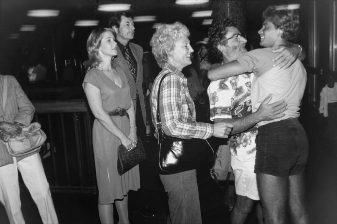 Black-and-white photograph of a man and a woman embracing in front of a smiling woman and another waiting couple