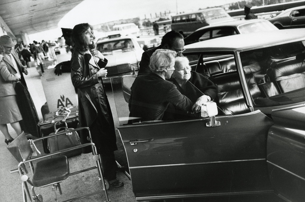 Black-and-white photograph of an elderly woman being helped into the passenger seat of a parked car