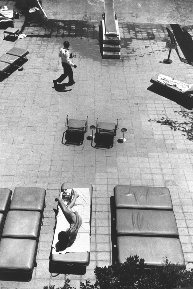 Black-and-white photograph taken from above of a man crossing a pool deck in front of a woman in a lounge chair