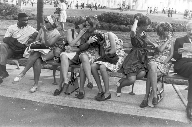 Black-and-white photograph of six young women on a park bench bordered by a young man conversing and an older man reading a newspaper