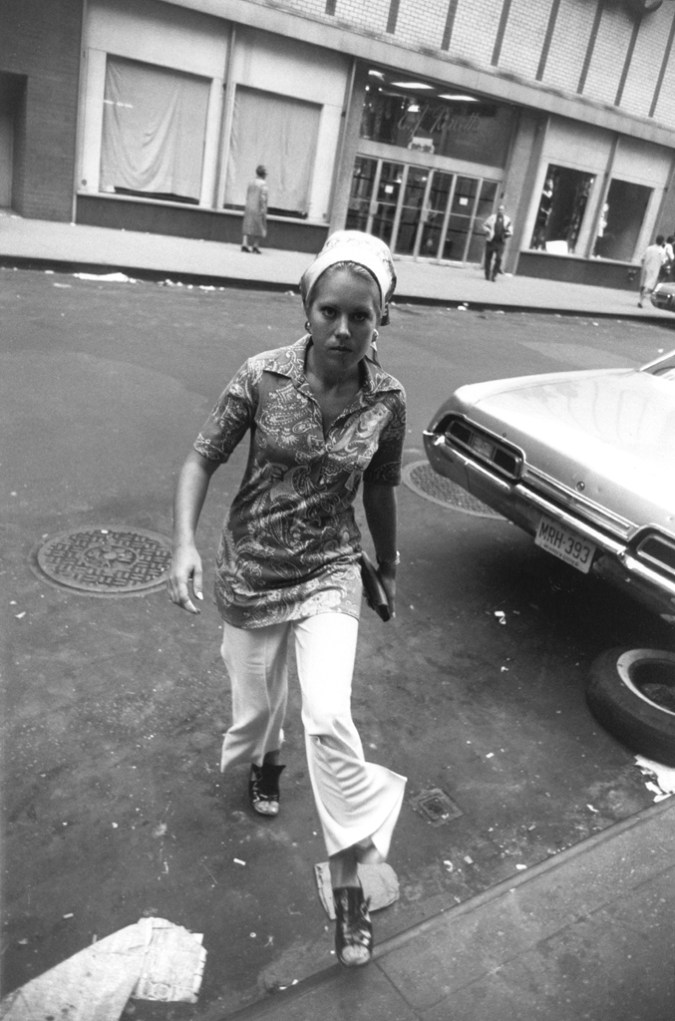 Black-and-white photograph of a woman stepping onto a curb with a storefront behind her