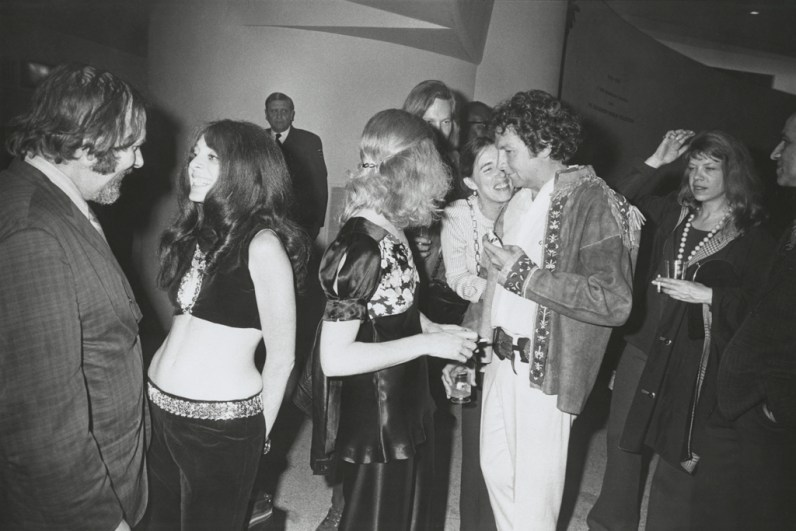 Black-and-white photograph of people having small conversations at a party
