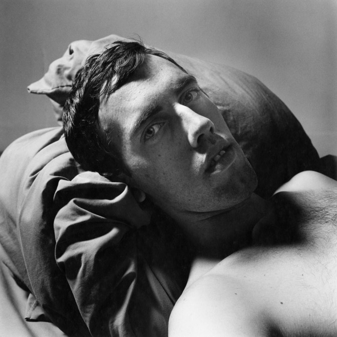 Black-and-white photograph of a shirtless man reclining on pillows
