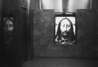 Black and white photograph of a building lobby with an image of Jesus Christ set into the marble wall