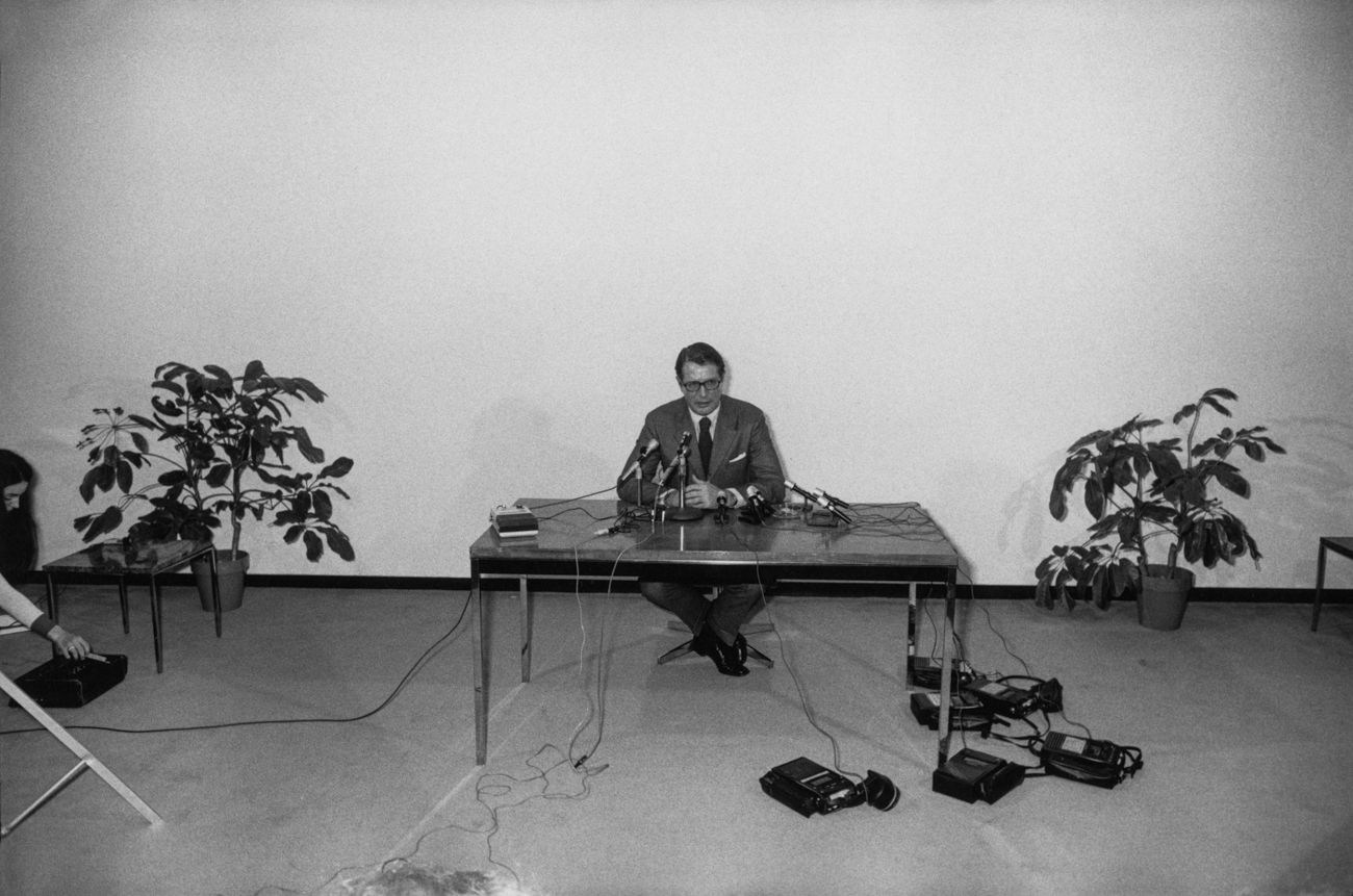 Black-and-white photograph of a man behind multiple microphones at a table against a blank wall