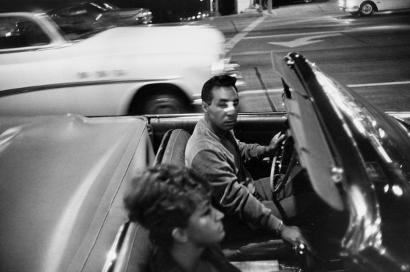 Black-and-white photograph of a man and woman in a moving convertible car