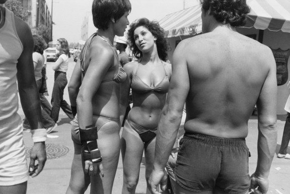 Black-and-white photograph of two women in bikinis with a man's back in the foreground