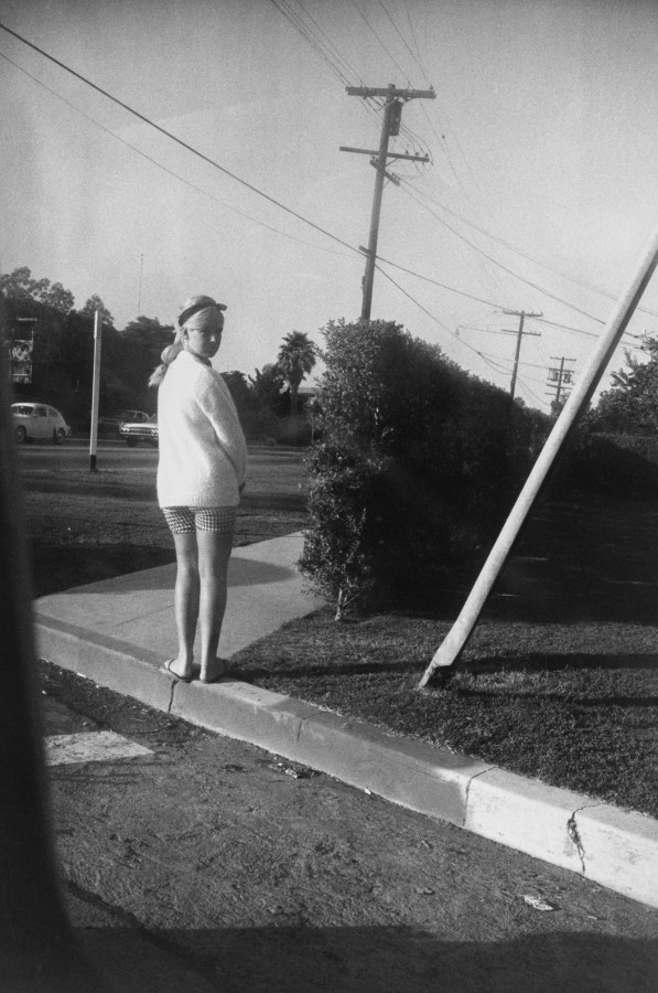 Black-and-white photograph of a woman standing on a curb next to a hedge