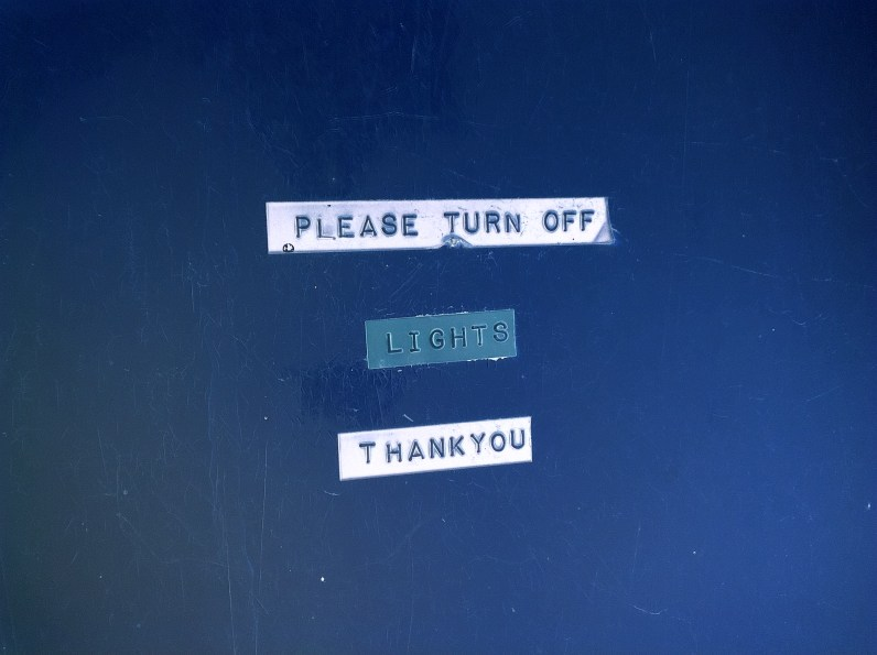 Inverted color photograph of labels on a wall reading PLEASE TURN OF LIGHTS THANK YOU