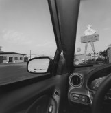 Black and white photograph of a car's dashboard and windscreen in a suburban setting